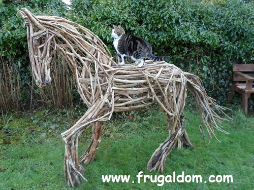 Scruffy the cat sitting on Angs, the wooden horse